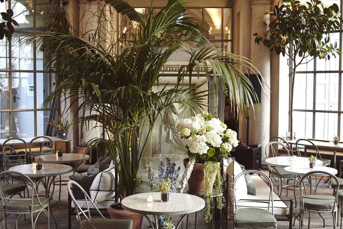 tavoli e sedie immerse tra alberi e fiori