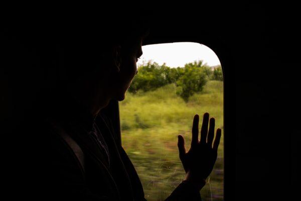Ragazzo meridionale guarda fuori dal finestrino del treno e con la mano saluta qualcuno.