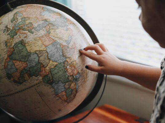 Bambino che osserva il mappamondo e indica uno dei posti in cui vorrebbe viaggiare.